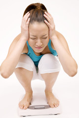 体重計にのって頭を抱える女性