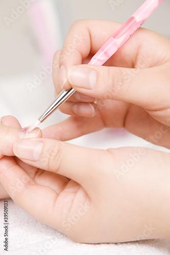 ネイルサロンでマニキュアを塗られる女性の手元