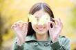 銀杏の葉を持って笑っている女性