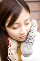 手袋で頬を暖める女性