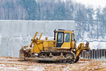 yellow bulldozer working in the winter
