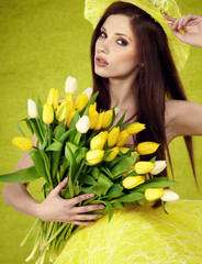 Young  woman hold yellow tulips flower on green