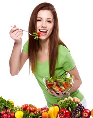Portrait of a pretty young woman eating vegetable salad against