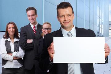 geschäftsleute mit hinweistafel vor firmengebäude