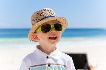 Happy boy in a straw hat on a tropical beach