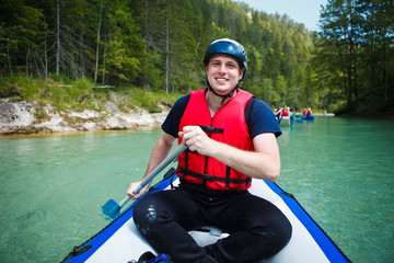 white water rafting - young man in a raft boat