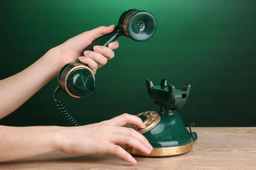 Dialing on retro phone on wooden table on green background