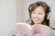 ヘッドホンで音楽を聴きながら本を読んでいる女性