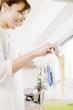 キッチンで鍋からトングでパスタの麺をすくう女性