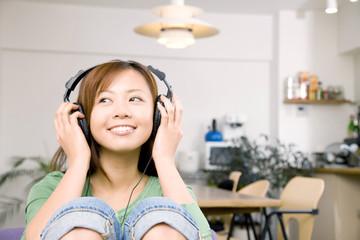 椅子に座りヘッドホンで音楽を聴いている女性