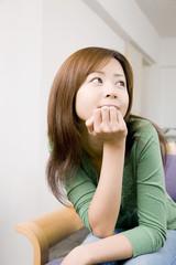 椅子に座り頬杖をつきながら考え事をしている女性