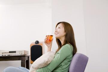 椅子に座りクッションを抱えながらお茶を飲んでいる女性
