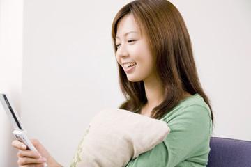 椅子に座りクッションを抱えながら携帯電話のメールを確認している女性