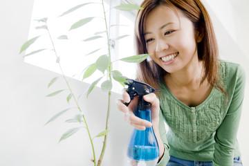 植物に霧吹きで水をあげる女性