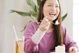 ケーキを食べながら笑っている女性