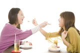 ケーキを食べ合いっこしている女性2人