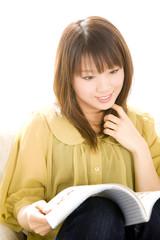 ソファに座り雑誌を見ている女性