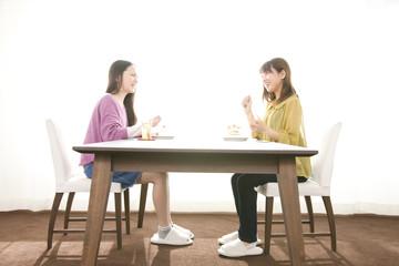 ダイニングでケーキを食べる女性2人