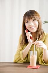 お茶を飲みながら携帯電話で通話している女性
