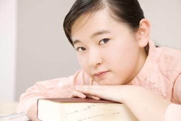 辞書に顔を伏せる女子中学生