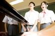 ピアノに合わせて歌う中学生男女