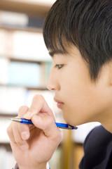 シャープペンシルを持って考え事をする男子中学生