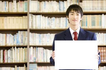 図書室でメッセージボードを持っている男子中学生