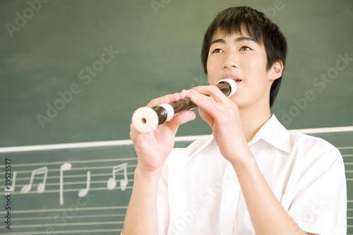 リコーダーを吹く男子中学生