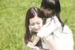 若い女性に後ろから抱きつく女の子
