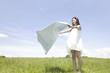 草原に敷き物をひく女性