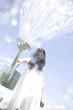 ジョウロで水を撒いている女性
