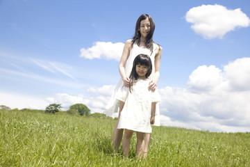 草原に立つ女の子と若い女性