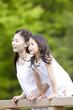 橋の上から景色を眺める女の子と若い女性