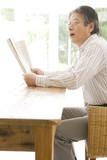 新聞を読みながら会話をするシニア男性