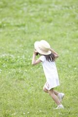 帽子を押さえながら走る女の子