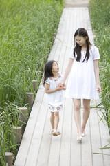 手を繋ぎ歩く女の子と若い女性