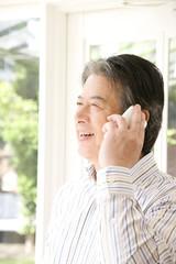 スマートフォンで話すシニア男性
