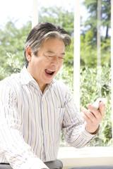 スマートフォンのメールを見るシニア男性
