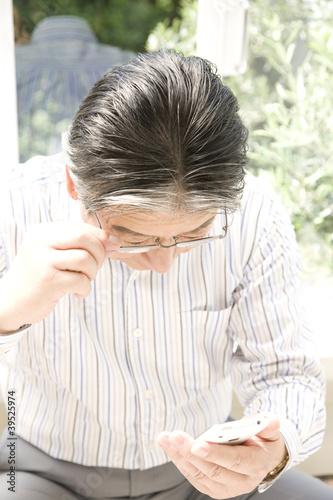 スマートフォンでメールを確認するシニア男性
