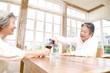 シニア女性のグラスにワイン注ぐシニア男性