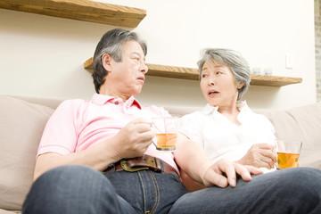ソファでお茶を飲むシニアカップル