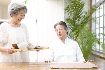 シニア男性に朝食を運ぶシニア女性