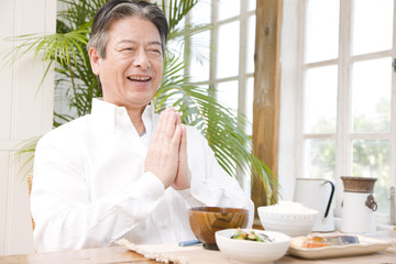 食事前に手を合わせるシニア男性
