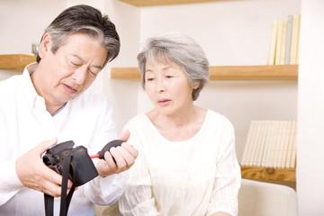 シニア女性と会話をしながらカメラの掃除をするシニア男性