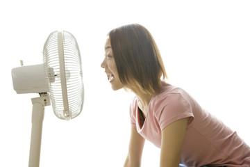 扇風機の風で涼む女性