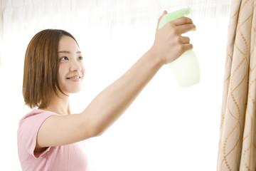 消臭スプレーをかける女性