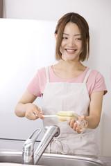 キッチンでグラスを洗う女性