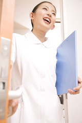 ドアを開ける笑顔の女性看護師