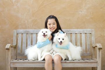 2匹のスピッツを抱き寄せ微笑む女の子