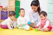 おもちゃで遊ぶ乳児3人と保育士
